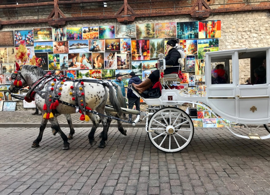 A tourist horse carriage crossing the Old Town Market area in Krakow
