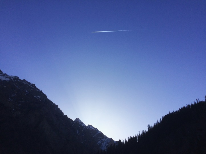 A plane crossing the sky over mountains