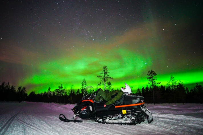Hunting Northern Lights on snowmobile in Rovaniemi in winter