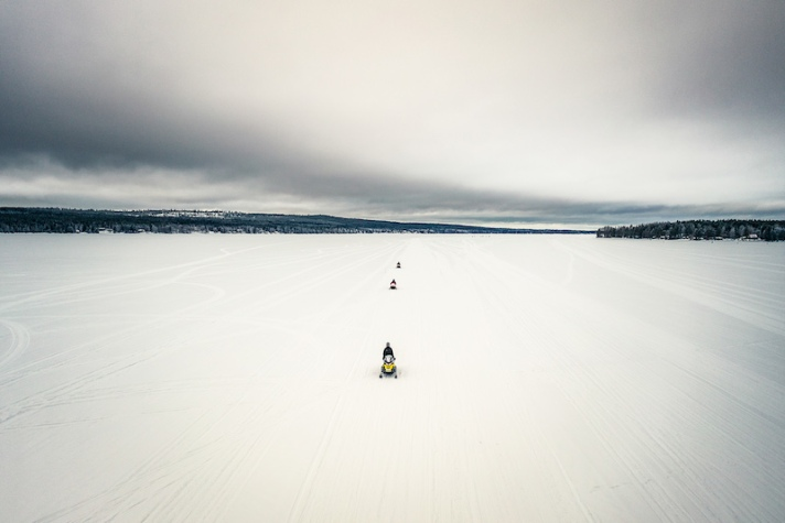 Snowmobile ride on a frozen lake in Rovaniemi in winter
